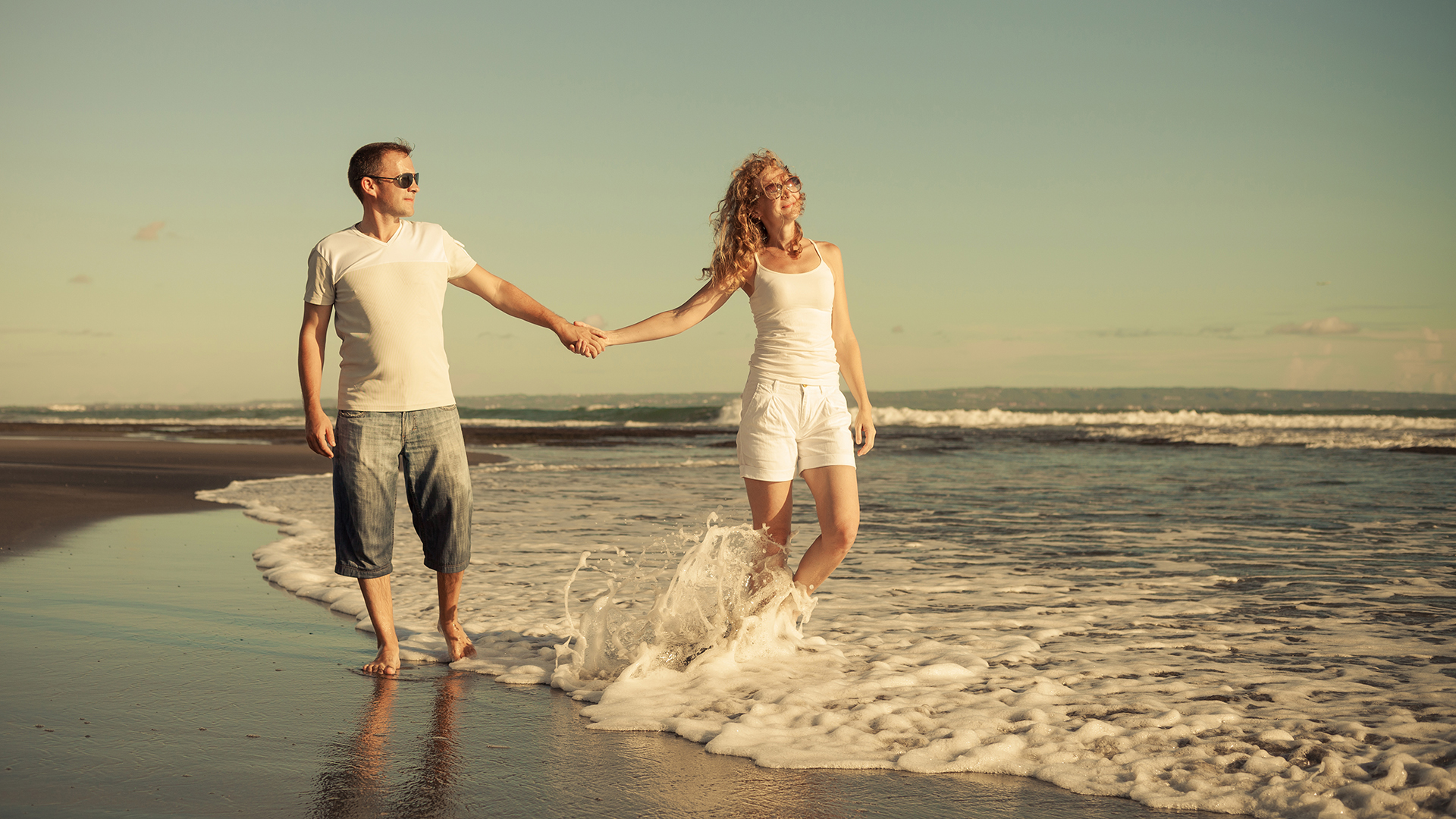 Romantic happy  man and woman couple walking on a  beach