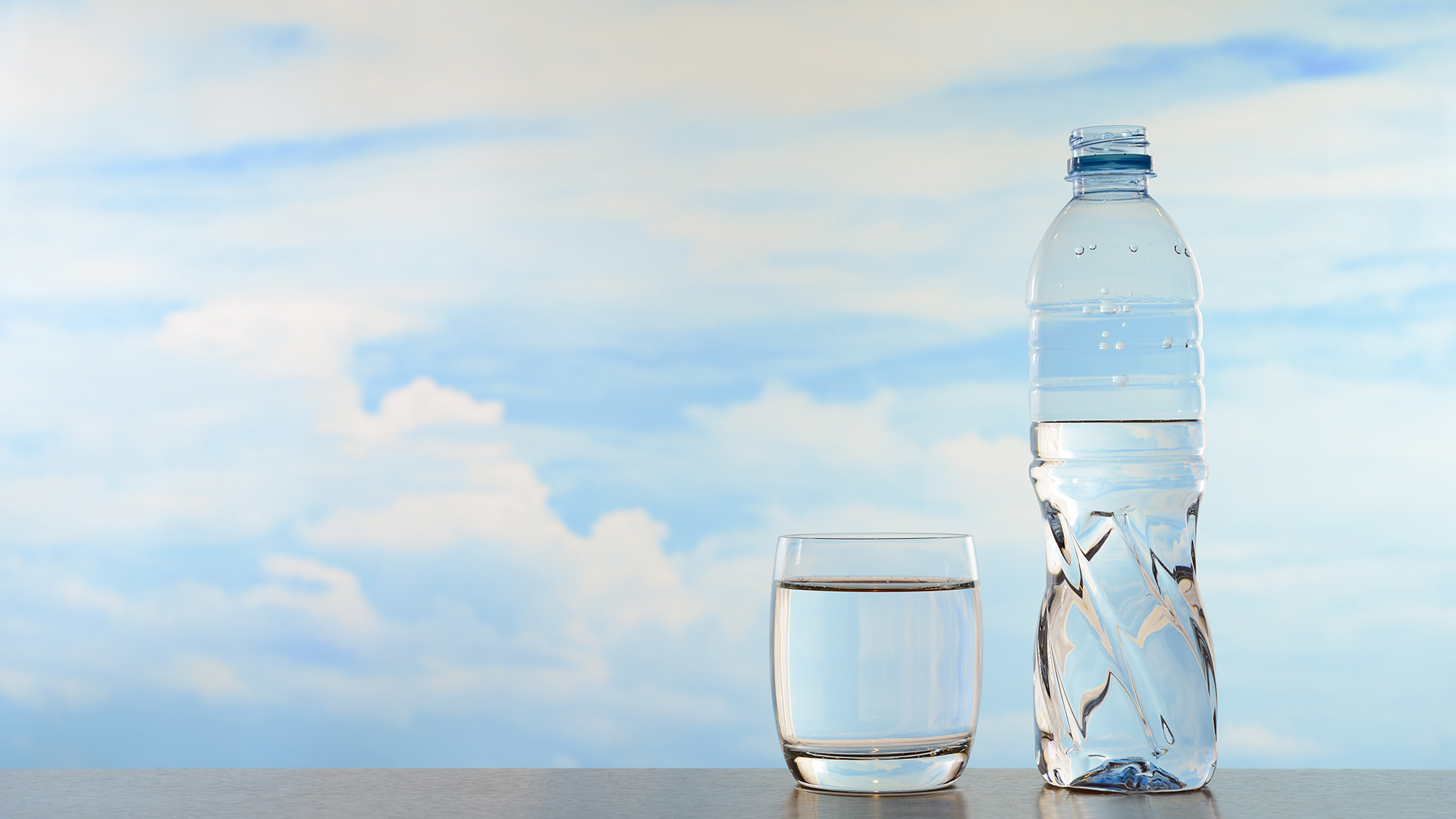 Fresh and clean drinking water in bottle and glass on sky background