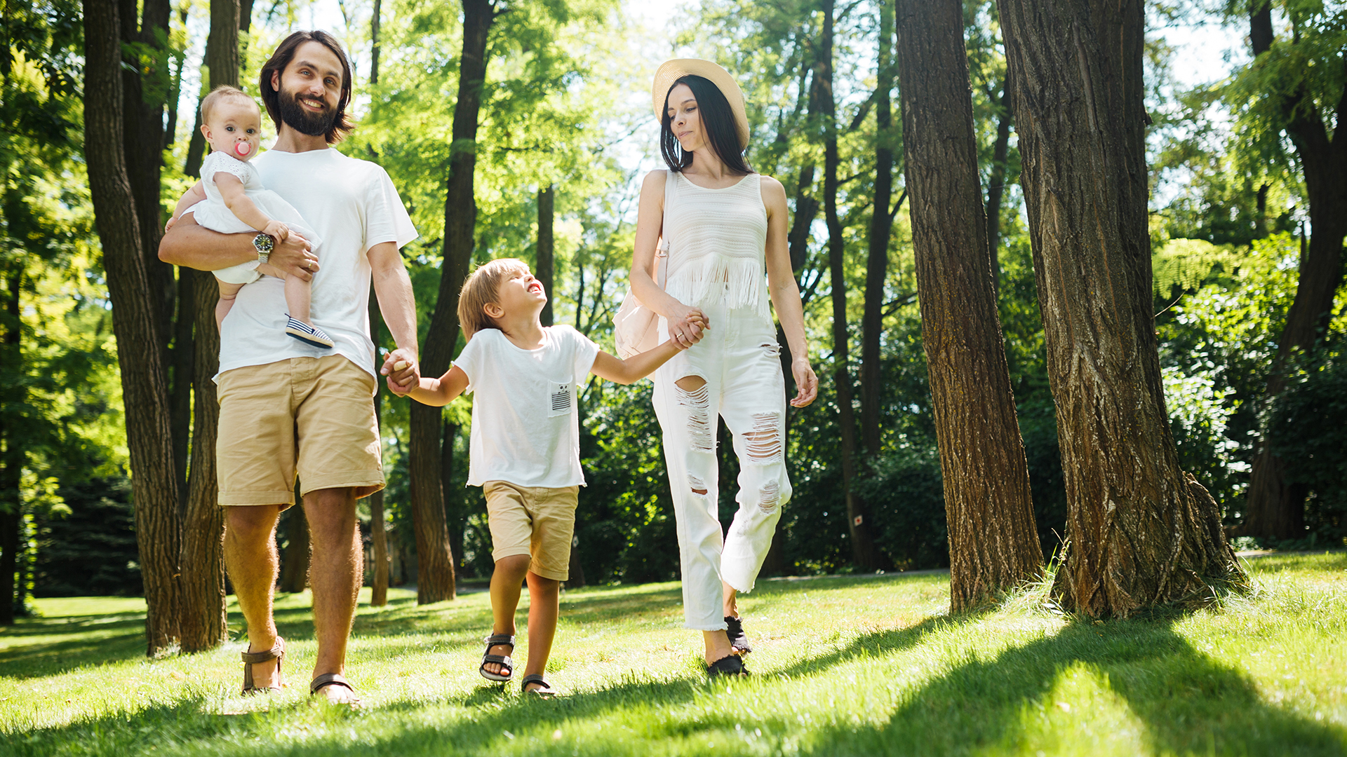Sunny summer day. Happy young family dressed in the white casual clothes walks in the park.