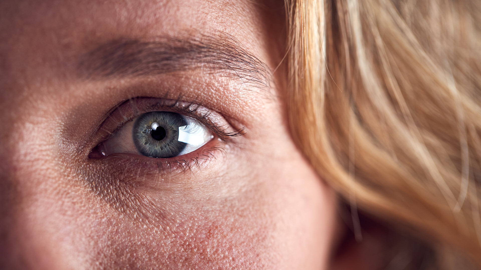 Close Up Of Eye Of Woman Looking Scared Against Black Studio Background